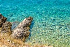 Haarscharfer blauer adriatisches Seefelsiger Strand Stockfoto