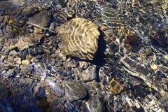 Haarscharfes Wasser über Kieseln und Steinen lizenzfreie stockfotos