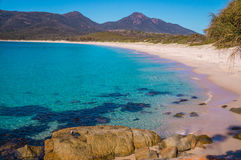 Haarscharfes Wasser der Weinglas-Bucht setzt, Tasmanien auf den Strand lizenzfreie stockfotografie