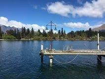 Haarscharfes Wasser des Queenstown-Ufergegendtürkises am sonnigen Tag Lizenzfreies Stockbild