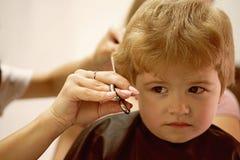 Haarschnitt, dass Ihr Kind liebt Nette Jungenfrisur Scherzt Friseursalon Kleines Kindergegebener Haarschnitt Kleines Kind herein lizenzfreies stockbild