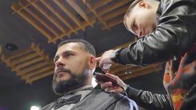 Haarschnittmänner Friseursalon Die Friseure der Männer; Friseure Friseur schneidet die Kundenmaschine für Haarschnitte Ansicht vo stock video footage