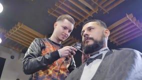 Haarschnittmänner Friseursalon Die Friseure der Männer; Friseure Friseur schneidet die Kundenmaschine für Haarschnitte Ansicht vo stock footage