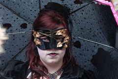 Masked woman in black carrying umbrella Stock Photo