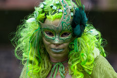 Masked woman wearing green outfit participates in Fantasy Fair Stock Photography