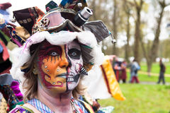 Woman with painted face and colorful outfit participates in Fantasy Fair Stock Photo