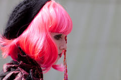 Woman wearing pink wig participates in Fantasy Fair Stock Image