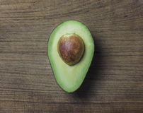 Haas Avocado. A ripe avocado cut in half with its pit on an old wooden cutting board Royalty Free Stock Images