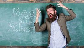Haatschool De leraar gaat gek over het scholen De leraar of de opvoeder bevinden zich dichtbij bord met inschrijving terug naar stock afbeelding