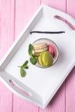 Haba coloreada de los macarrones, de la menta y de vainilla en un fondo de madera rosado Imagenes de archivo