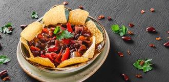 Haba roja con nachos o microprocesadores de la pita, pimienta y verdes en la placa sobre fondo oscuro Bocado mexicano, comida veg foto de archivo libre de regalías