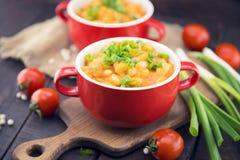 Habas blancas en salsa de tomate en un cuenco de cerámica rojo en la madera rústica Fotografía de archivo libre de regalías