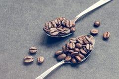 Habas de Coffe en las cucharas de acero en negro Imagen de archivo libre de regalías