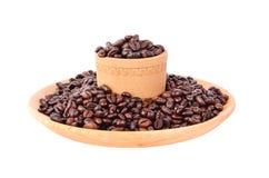Habas de Coffe en una taza de madera Fotos de archivo