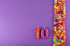 Habas de jalea coloridas con las velas para la torta 10mo aniversario del año foto de archivo