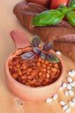 Habas de riñón blancas asadas con los tomates y albahaca en un pote Imágenes de archivo libres de regalías