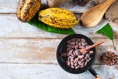 Habas del cacao y vainas crudas del cacao en los tableros de madera fotografía de archivo