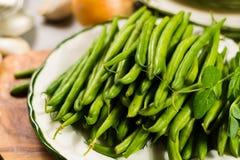 Habas rápidas verdes frescas en la placa lista para guisar Fotografía de archivo