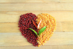 Habas rojas con pelado - las habas partidas de la soja hicieron símbolo del corazón en el fondo de madera Fotos de archivo