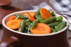 Habas verdes con las zanahorias cortadas en un pote para cocer Imagen de archivo libre de regalías