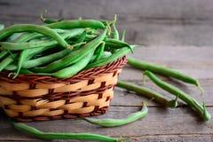 Habas verdes crudas frescas en una cesta marrón y en una tabla de madera del vintage Foto joven de las vainas de habas Cosecha ve foto de archivo