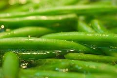 Habas verdes en agua hirvienda Imágenes de archivo libres de regalías