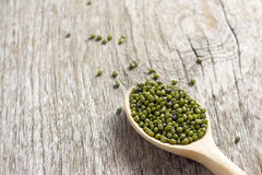 Habas verdes en cuchara en el piso de madera, cereal en piso de madera Imagen de archivo