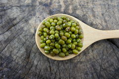 Habas verdes en una cuchara de madera Foto de archivo
