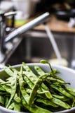 Habas verdes frescas lavadas en la cocina Foto de archivo