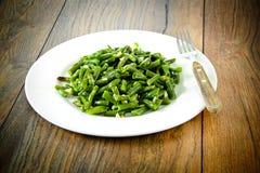 Habas verdes fritas con ajo en una placa blanca foto de archivo libre de regalías