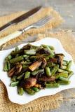 Habas verdes fritas deliciosas con las setas y las especias en una placa, bifurcación, cuchillo, arpillera en viejo fondo de made Imagen de archivo libre de regalías