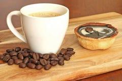 Habas y café asados en una taza blanca Imagen de archivo