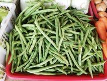 Habas y otras verduras exhibidas en parada imagen de archivo libre de regalías