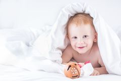 Habby young smilling child boy in white bed.  stock image