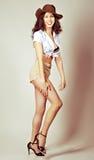 Haben langes Haarmädchen des Brunette den Spaß, der im Studio im Cowboyschweinestall aufwirft stockbilder