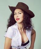 Haben langes Haarmädchen des Brunette den Spaß, der im Studio im Cowboyschweinestall aufwirft lizenzfreies stockfoto