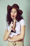 Haben langes Haarmädchen des Brunette den Spaß, der mit Gewehr im Studio in c aufwirft stockfotografie