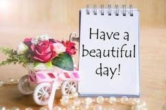 Haben Sie einen schönen Tag auf offenem Tagebuch und und Rotrose Stockbild