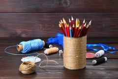 Haben Sie für Bleistifte mit den Herzen ein Bankkonto, die mit Schnur auf einem hölzernen Vorsprung eingewickelt werden Stockfoto