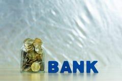 HABEN Sie Text mit Münzgeld im Glasgefäß auf Tabelle, für die Rettung ein Bankkonto Lizenzfreie Stockfotos