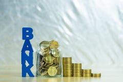 HABEN Sie Text mit Münzgeld im Glasgefäß auf Tabelle, für die Rettung ein Bankkonto Stockbild