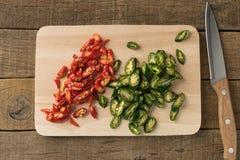 Haber cortado rojo y verde de la pimienta de chiles y cuchillos en tablas de cortar Imagenes de archivo