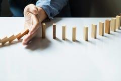 haber derribado continuo o riesgo de los dominós de la parada de la mano del hombre de negocios con c imagenes de archivo