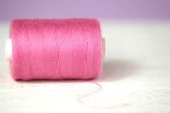 Haberdashery pink thread on white and lilac background Stock Images