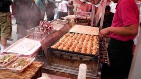 Habilidad del takoyaki del cocinero con los palillos almacen de video