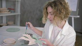 Habilidade do oleiro, retrato da mulher inspirador nova do artesão que trabalha com a placa recentemente terminada da cerâmica e  filme