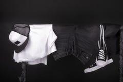 Habillement accrochant Les espadrilles noires et blanches, jeans de chapeau sur des vêtements étirent le fond Copiez l'espace Photographie stock