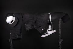 Habillement accrochant Les espadrilles noires et blanches, jeans de chapeau sur des vêtements étirent le fond Copiez l'espace Photo stock