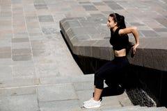 Habillement de port de sport de fille impressionnante de forme physique s'étendant à la ville L'espace pour le texte photos stock