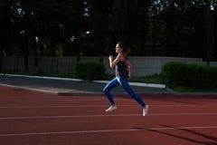 Habillement de port de sport de fille sportive fonctionnant au stade vide à la soirée L'espace pour le texte image libre de droits